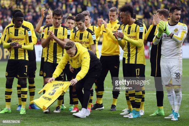 Marco Reus of Dortmund lays down the jersey of injured team mate Marc Bartra after winning the Bundesliga match between Borussia Dortmund and...