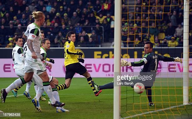 Marco Reus of Dortmund scores his teams first goal past goalkeeper Diego Benaglio of Wolfsburg during the Bundesliga match between Borussia Dortmund...