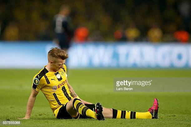 Marco Reus of Dortmund sits injured on the pitch during the DFB Cup Final 2016 between Bayern Muenchen and Borussia Dortmund at Olympiastadion on May...