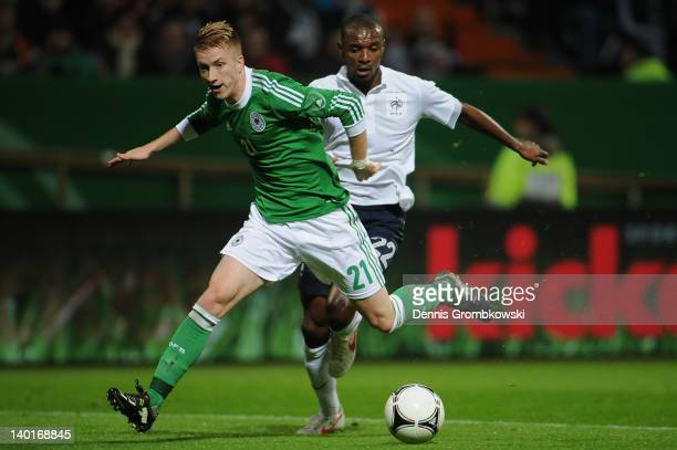 Marco Reus of Germany is chased by Eric Abidal of France during the International friendly match between Germany and France at Weser Stadium on...