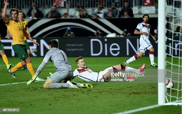 Marco Reus of Germany scores the opening goal past goalkeeper Mathew Ryan of Australia during the International Friendly match between Germany and...