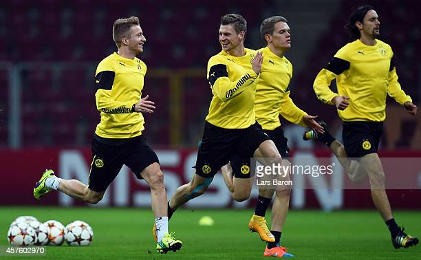 Marco Reus sprints with Lukasz Piszczek during a Borussia Dortmund training session ahead of their Champions League match against Galatasaray AS at...