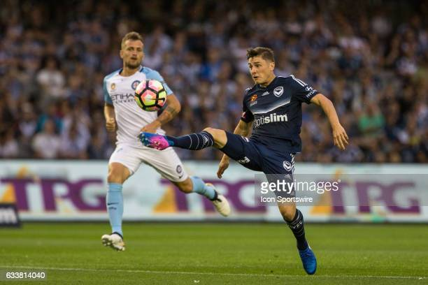 Marco Rojas of Melbourne Victory lobs the ball over Dean Bouzanis of Melbourne City during a contest with Michael Jakobsen of Melbourne City during...