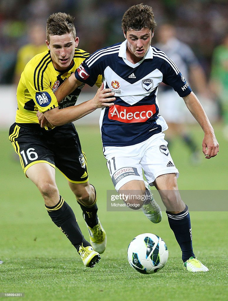 Marco Rojas of the Melbourne Victory runs with the ball against Louis Fenton (L) of the Wellington Phoenix during the round 15 A-League match between the Melbourne Victory and Wellington Phoenix at AAMI Park on January 5, 2013 in Melbourne, Australia.
