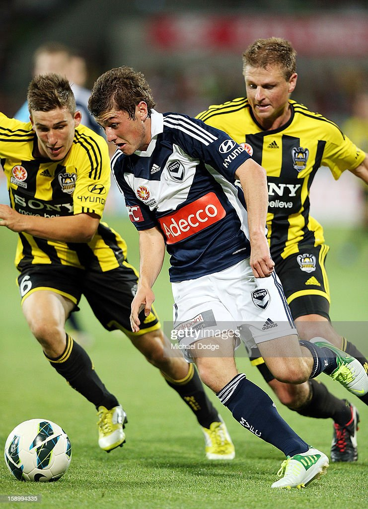 Marco Rojas of the Melbourne Victory runs with the ball next to Alex Smith (L) of the Wellington Phoenix during the round 15 A-League match between the Melbourne Victory and Wellington Phoenix at AAMI Park on January 5, 2013 in Melbourne, Australia.