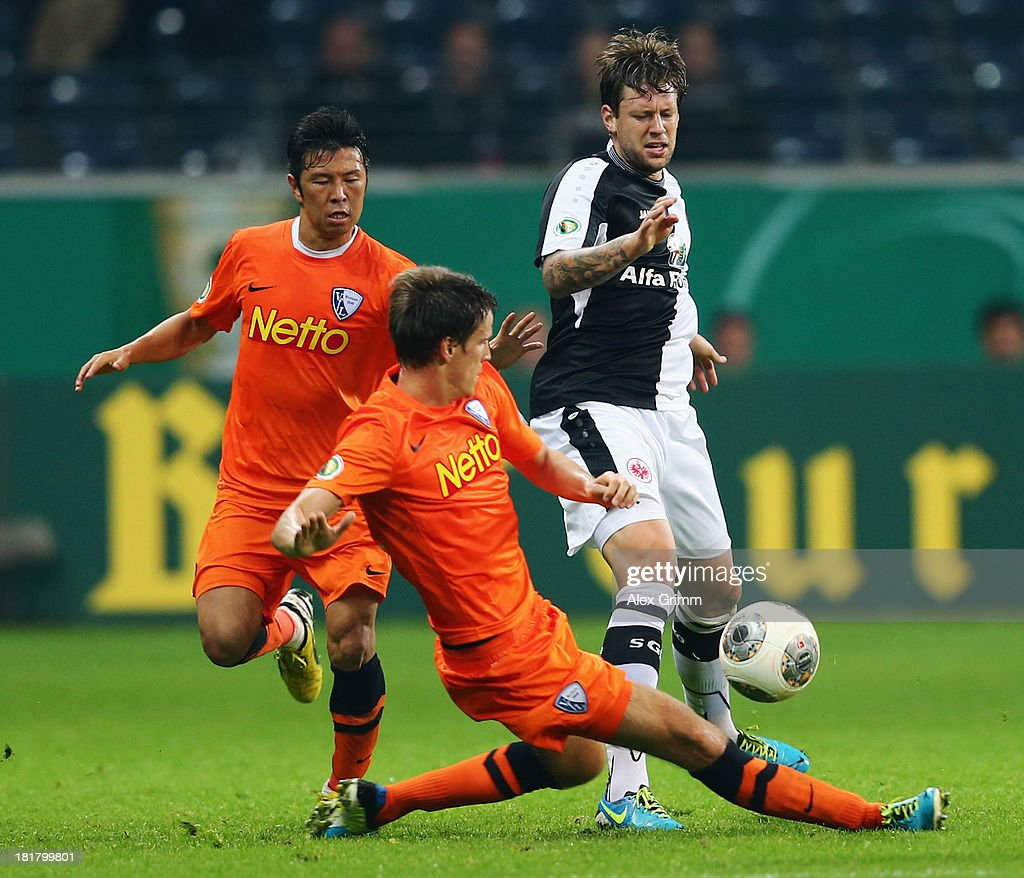 Marco Russ (R) of Frankfurt is challenged by Jonas Acquistapace (front) and Yusuke Tasaka of Bochum during the DFB Cup second round match between Eintracht Frankfurt and VfL Bochum at Commerzbank-Arena on September 25, 2013 in Frankfurt am Main, Germany.
