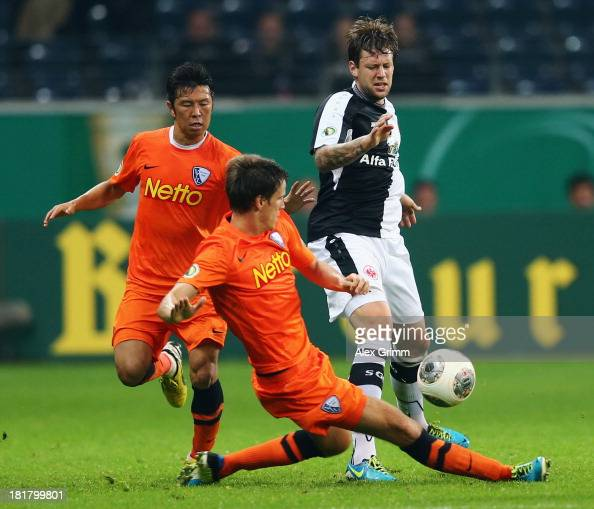 Marco Russ of Frankfurt is challenged by Jonas Acquistapace and Yusuke Tasaka of Bochum during the DFB Cup second round match between Eintracht...