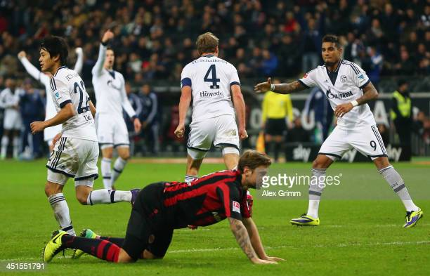 Marco Russ of Frankfurt reacts as Benedikt Hoewedes of Schalke celebrates his team's third goal with team mates during the Bundesliga match between...