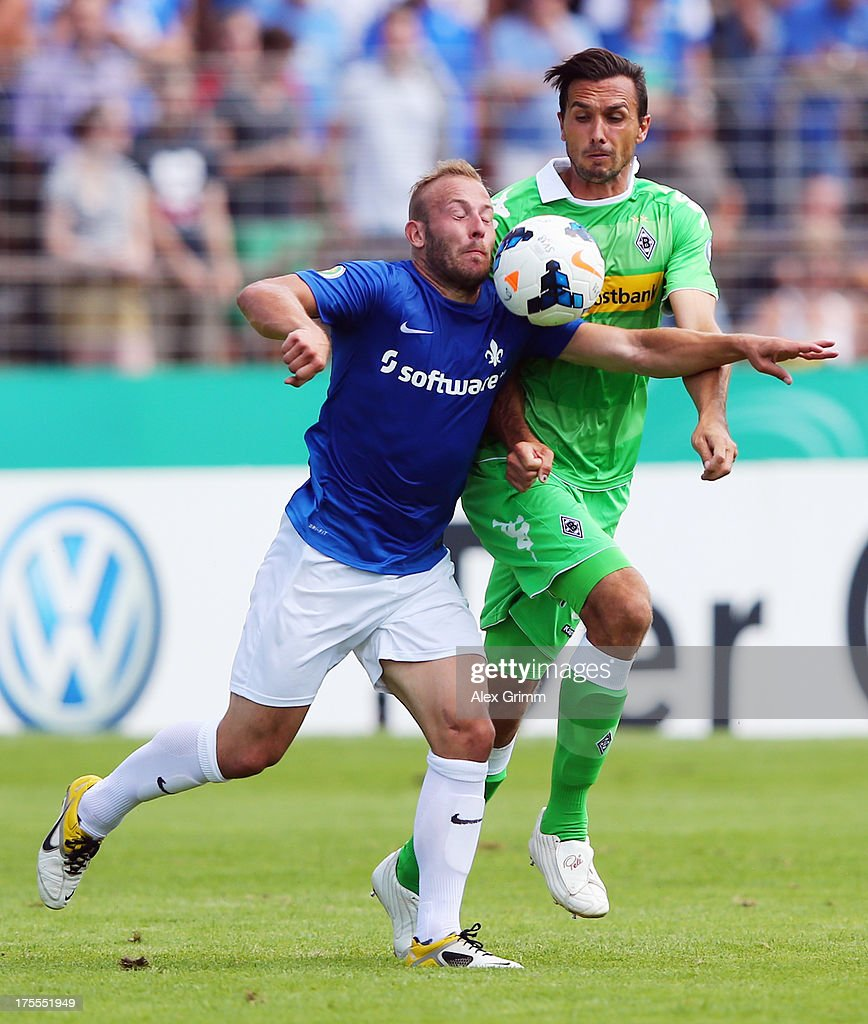 Marco Sailer (front) of Darmstadt is challenged by <a gi-track='captionPersonalityLinkClicked' href=/galleries/search?phrase=Martin+Stranzl&family=editorial&specificpeople=674140 ng-click='$event.stopPropagation()'>Martin Stranzl</a> of Moenchengladbach during the DFB Cup first round match between Darmstadt 98 and Borussia Moenchengladbach at Boellenfalltorstadion on August 4, 2013 in Darmstadt, Germany.