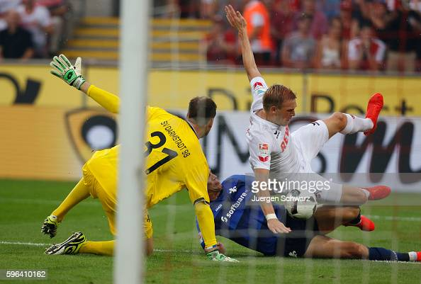 Marco Sailer of Darmstadt tackles Artjoms Rudnevs of Cologne watched by goalkeeper Michael Esser during the Bundesliga match between 1 FC Koeln and...