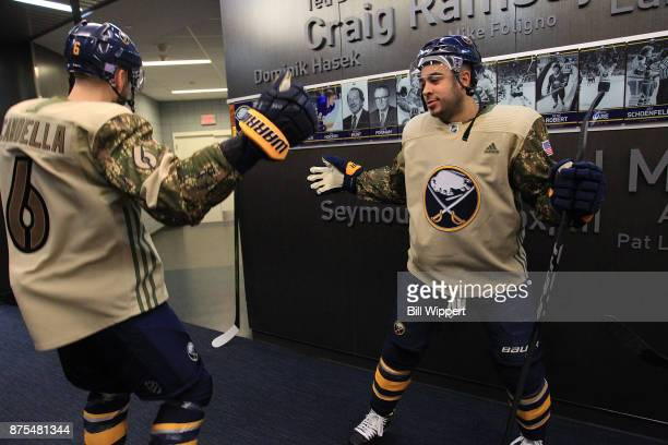 Marco Scandella and Nicholas Baptiste of the Buffalo Sabres prepare to take the ice wearing special jerseys on Military Appreciation Night before an...