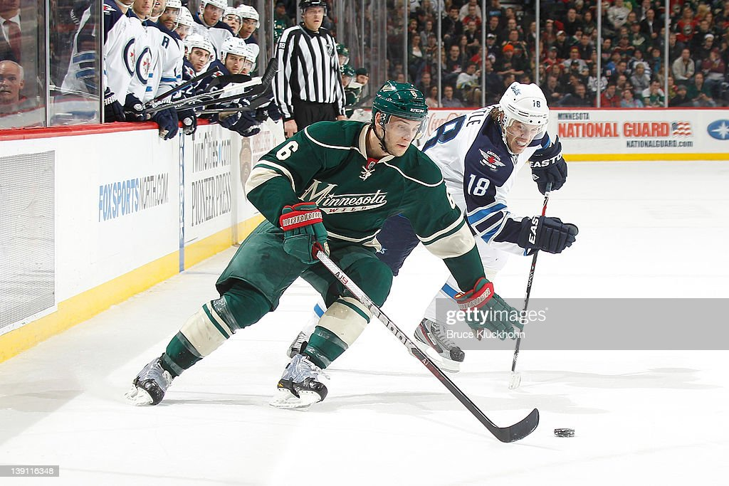 Marco Scandella #6 of the Minnesota Wild skates with the puck while <a gi-track='captionPersonalityLinkClicked' href=/galleries/search?phrase=Bryan+Little&family=editorial&specificpeople=540533 ng-click='$event.stopPropagation()'>Bryan Little</a> #18 of the Winnipeg Jets defends during the game at the Xcel Energy Center on February 16, 2012 in St. Paul, Minnesota.