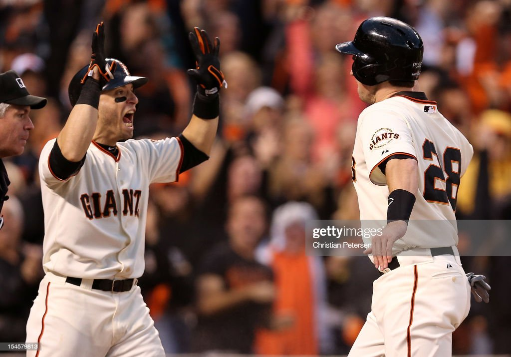 Marco Scutaro #19 and Buster Posey #28 of the San Francisco Giants celebrate after scoring in the third inning on a three-run double by Hunter Pence #8 against the St. Louis Cardinals in Game Seven of the National League Championship Series at AT&T Park on October 22, 2012 in San Francisco, California.