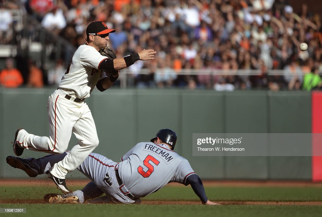 <a gi-track='captionPersonalityLinkClicked' href=/galleries/search?phrase=Marco+Scutaro&family=editorial&specificpeople=239523 ng-click='$event.stopPropagation()'>Marco Scutaro</a> #19 of the San Francisco Giants did not get his throw off in time to complete the double play while avoiding the slide of <a gi-track='captionPersonalityLinkClicked' href=/galleries/search?phrase=Freddie+Freeman&family=editorial&specificpeople=5743987 ng-click='$event.stopPropagation()'>Freddie Freeman</a> #5 of the Atlanta Braves in the first inning at AT&T Park on August 26, 2012 in San Francisco, California. Michael Bourn #24 of the Braves scored on the play.