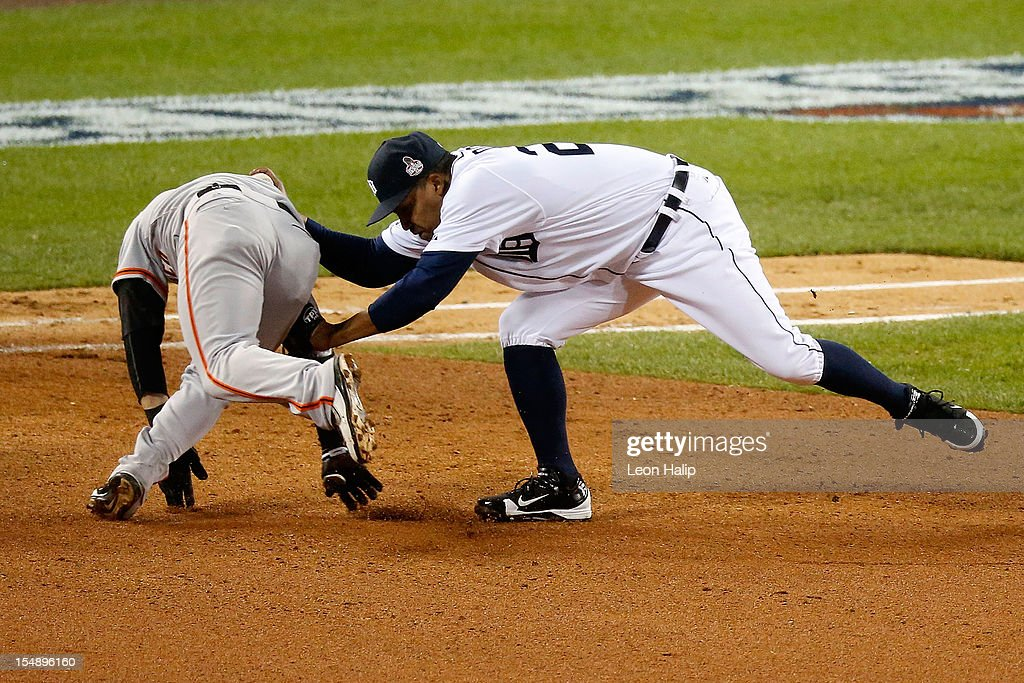 Marco Scutaro #19 of the San Francisco Giants gets tagged in a rundown against Octavio Dotel #20 of the Detroit Tigers and Jhonny Peralta #27 in the eighth inning during Game Four of the Major League Baseball World Series at Comerica Park on October 28, 2012 in Detroit, Michigan.