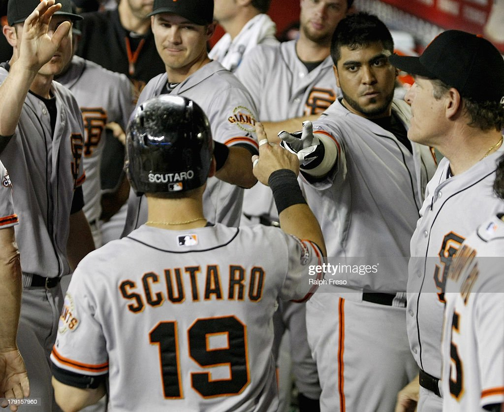 <a gi-track='captionPersonalityLinkClicked' href=/galleries/search?phrase=Marco+Scutaro&family=editorial&specificpeople=239523 ng-click='$event.stopPropagation()'>Marco Scutaro</a> #19 of the San Francisco Giants is congratulated by Hector Sanchez #29 (R) and teammates after scoring against the Arizona Diamondbacks during the seventh inning of a MLB game at Chase Field on August 31, 2013 in Phoenix, Arizona.