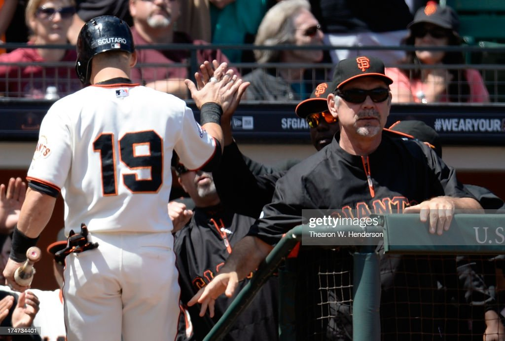 Marco Scutaro #19 of the San Francisco Giants is congratulated by manager Bruce Bochy #15 after Scutaro scored in the fifth inning against the Chicago Cubs at AT&T Park on July 28, 2013 in San Francisco, California.