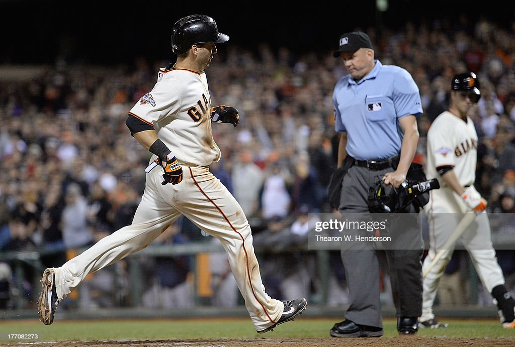 <a gi-track='captionPersonalityLinkClicked' href=/galleries/search?phrase=Marco+Scutaro&family=editorial&specificpeople=239523 ng-click='$event.stopPropagation()'>Marco Scutaro</a> #19 of the San Francisco Giants scores on a sacrifice fly from Buster Posey #28 in the eighth inning against the Boston Red Sox at AT&T Park on August 20, 2013 in San Francisco, California. Scutaro's score tied the game 2-2.