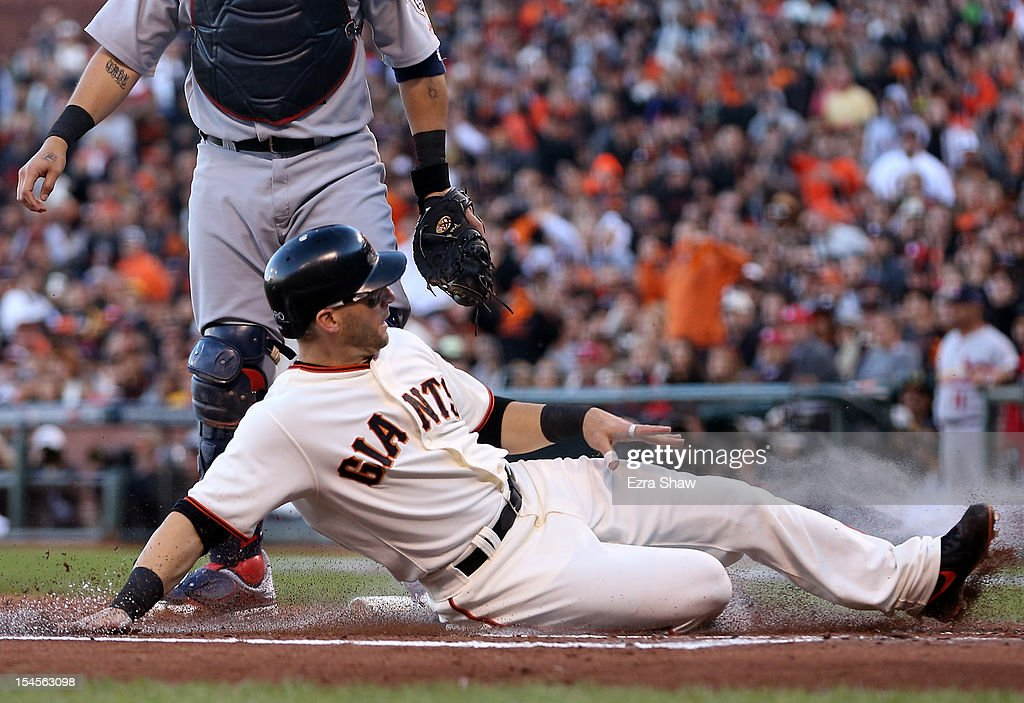 <a gi-track='captionPersonalityLinkClicked' href=/galleries/search?phrase=Marco+Scutaro&family=editorial&specificpeople=239523 ng-click='$event.stopPropagation()'>Marco Scutaro</a> #19 of the San Francisco Giants slides home as Scutaro scores in the first inning against the St. Louis Cardinals in Game Six of the National League Championship Series at AT&T Park on October 21, 2012 in San Francisco, California.