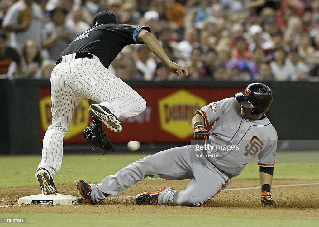 <a gi-track='captionPersonalityLinkClicked' href=/galleries/search?phrase=Marco+Scutaro&family=editorial&specificpeople=239523 ng-click='$event.stopPropagation()'>Marco Scutaro</a> #19 of the San Francisco Giants slides into third base with a triple as <a gi-track='captionPersonalityLinkClicked' href=/galleries/search?phrase=Eric+Chavez&family=editorial&specificpeople=201561 ng-click='$event.stopPropagation()'>Eric Chavez</a> #12 of the Arizona Diamondbacks tries to field the throw during the seventh inning of a MLB game at Chase Field on August 31, 2013 in Phoenix, Arizona.