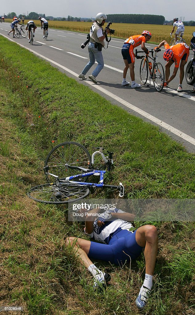 Marco Velo of Italy and riding for Fassa Bortolo lies on the side of the road injured as Iban Mayo of Spain and riding for Euskatel Euskadi gets help...