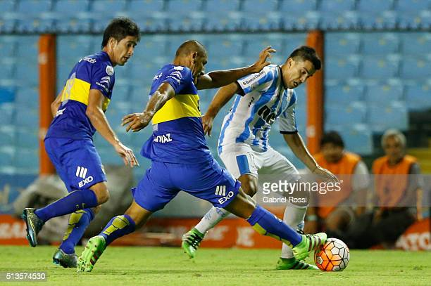 Marcos Acuña of Racing Club fights for the ball with Daniel Diaz of Boca Juniors during a group stage match between Boca Juniors and Racing Club as...