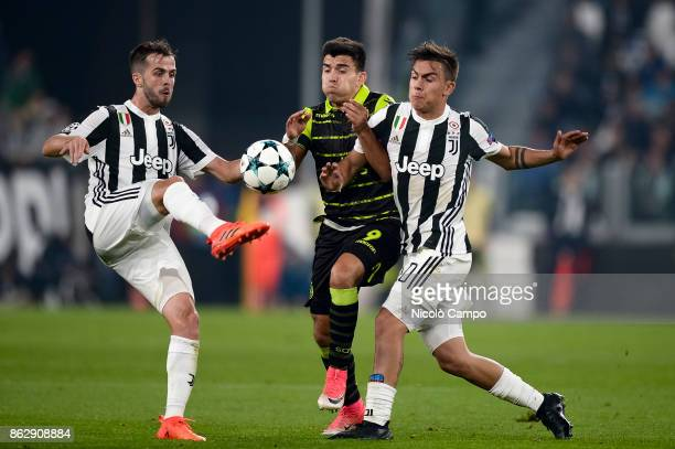 Marcos Acuna of Sporting CP compete with Miralem Pjanic and Paulo Dybala of Juventus FC during the UEFA Champions League football match between...