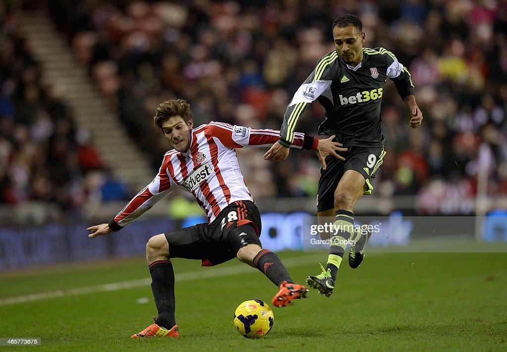 Marcos Alonso of Sunderland is tackled by Peter Odemwingie of Stoke City during the Premier League match between Sunderland and Stoke City at Stadium of Light on January 29, 2014 in Sunderland, England.