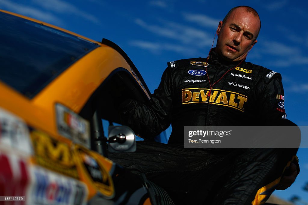 <a gi-track='captionPersonalityLinkClicked' href=/galleries/search?phrase=Marcos+Ambrose&family=editorial&specificpeople=179434 ng-click='$event.stopPropagation()'>Marcos Ambrose</a>, driver of the #9 DeWalt Ford, climbs from his car during qualifying for the NASCAR Sprint Cup Series Advocare 500 at Phoenix International Raceway on November 8, 2013 in Avondale, Arizona.
