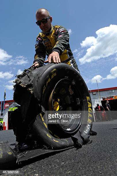 Marcos Ambrose driver of the DeWalt Ford looks at a worn tire during practice for the NASCAR Sprint Cup Series Aaron's 499 at Talladega Superspeedway...