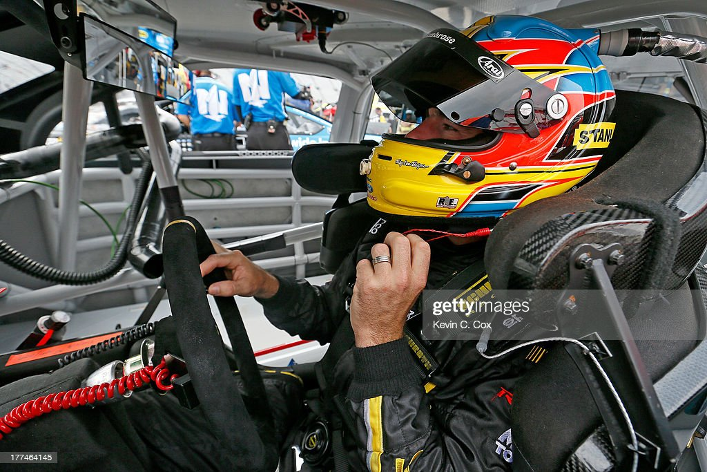 Marcos Ambrose, driver of the #9 Stanley Ford, adjusts his helmet in his car during practice for the NASCAR Sprint Cup Series IRWIN Tools Night Race at Bristol Motor Speedway on August 23, 2013 in Bristol, Tennessee.