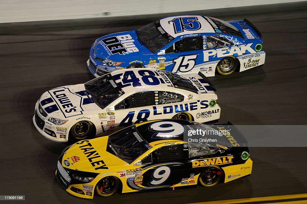 Marcos Ambrose, driver of the #9 Stanley Ford, Jimmie Johnson, driver of the #48 Lowe's Dover White Chevrolet, and Clint Bowyer, driver of the #15 Blue DEF Diesel Exhaust Fluid Toyota, race during the NASCAR Sprint Cup Series Coke Zero 400 at Daytona International Speedway on July 6, 2013 in Daytona Beach, Florida.