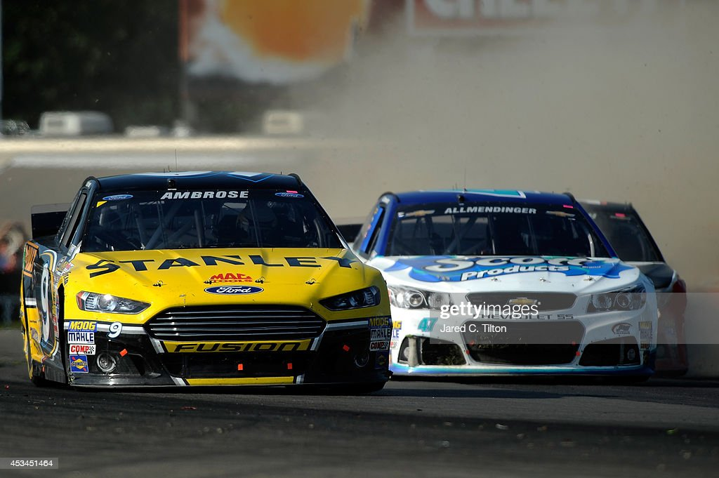 Marcos Ambrose, driver of the #9 Stanley Ford, passes AJ Allmendinger, driver of the #47 Scott Products Chevrolet, during the NASCAR Sprint Cup Series Cheez-It 355 at Watkins Glen International on August 10, 2014 in Watkins Glen, New York.