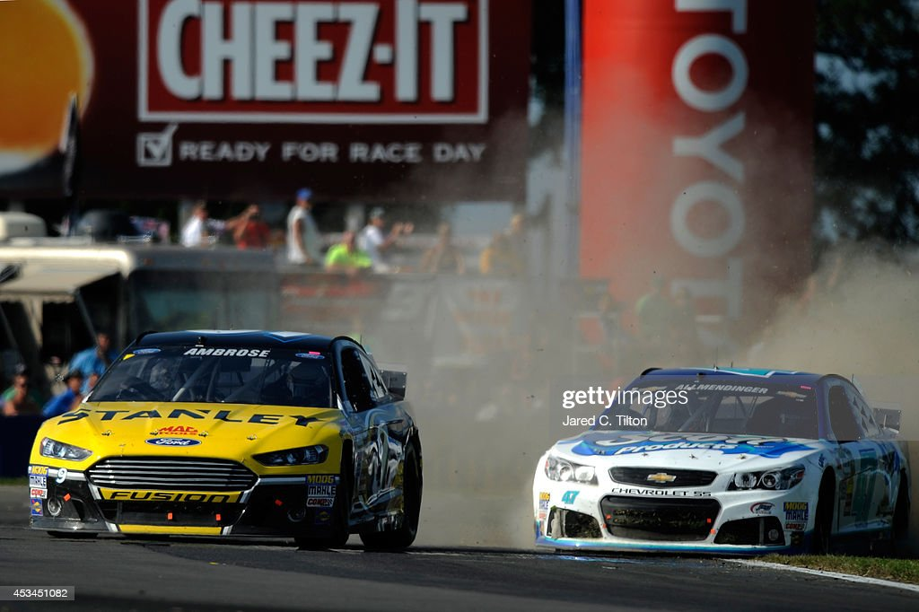 Marcos Ambrose, driver of the #9 Stanley Ford, races AJ Allmendinger, driver of the #47 Scott Products Chevrolet, during the NASCAR Sprint Cup Series Cheez-It 355 at Watkins Glen International on August 10, 2014 in Watkins Glen, New York.