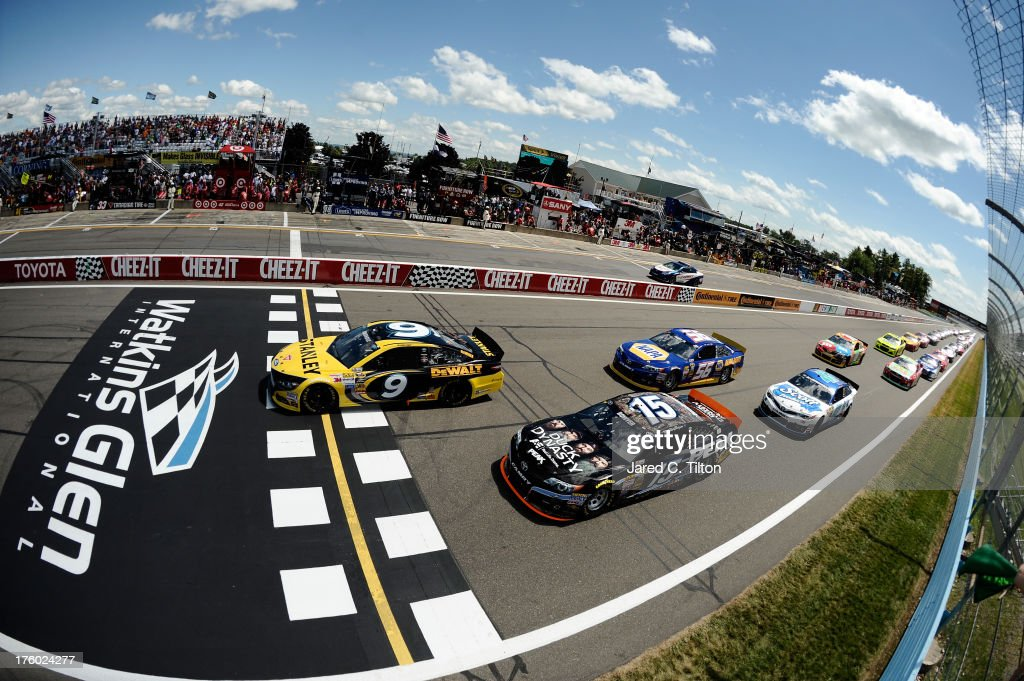 Marcos Ambrose, driver of the #9 Stanley/CTC Jumpstart Ford, leads Clint Bowyer, driver of the #15 PEAK/Duck Dynasty Toyota, to start the race during the NASCAR Sprint Cup Series Cheez-It 355 at The Glen at Watkins Glen International on August 11, 2013 in Watkins Glen, New York.