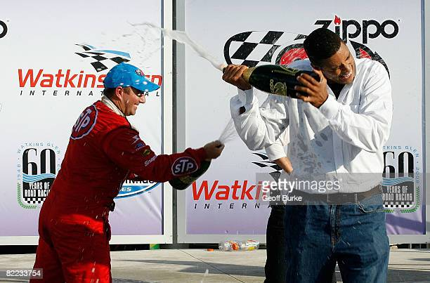 Marcos Ambrose driver of the STP Ford celebrates with team coowner Brad Daugherty after winning the NASCAR Nationwide Series Zippo 200 at the Watkins...