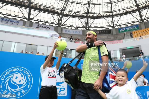 Marcos Baghdatis of Cyprus enters a court with a kid during the semi final match against Guido Pella of Argentina during Day 6 of 2017 ATP Chengdu...
