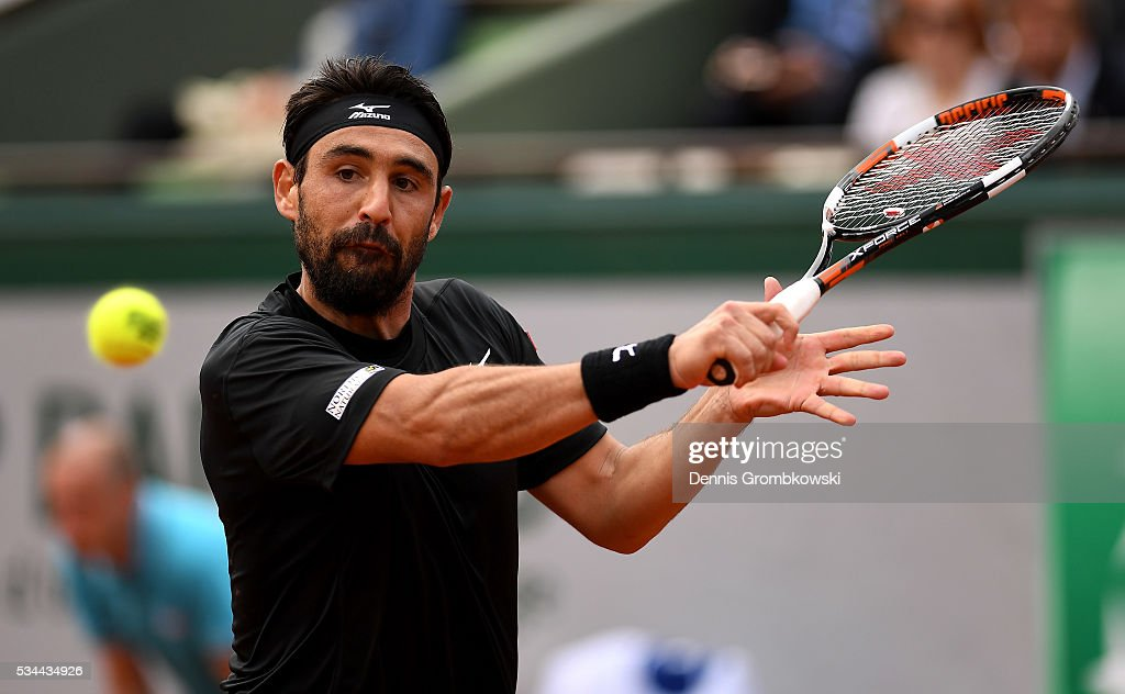 Marcos Baghdatis of Cyprus hits a backhand during the Men's Singles second round match against Jo-Wilfried Tsonga of France on day five of the 2016 French Open at Roland Garros on May 26, 2016 in Paris, France.