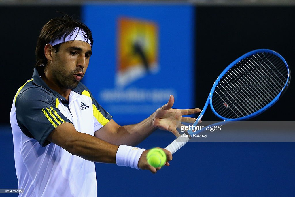 Marcos Baghdatis of Cyprus plays a backhand in his first round match against Albert Ramos of Spain during day one of the 2013 Australian Open at Melbourne Park on January 14, 2013 in Melbourne, Australia.