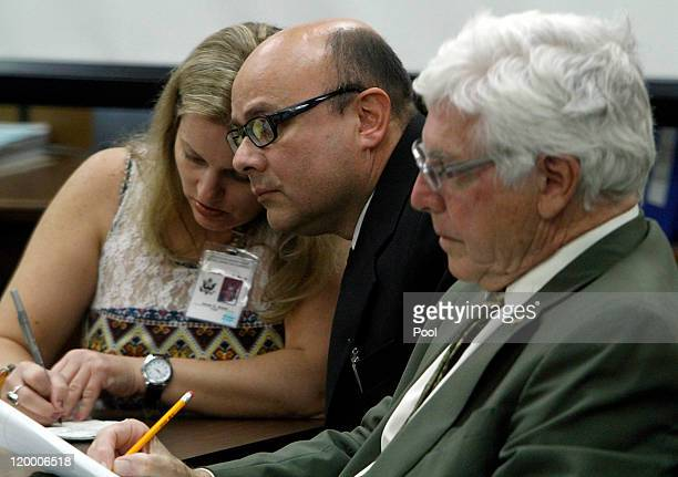 Marcos Costa listens to court appointed interpreter Teresa Krakow as defense attorney Edward Murphy listens as she explains why the jury was sent...