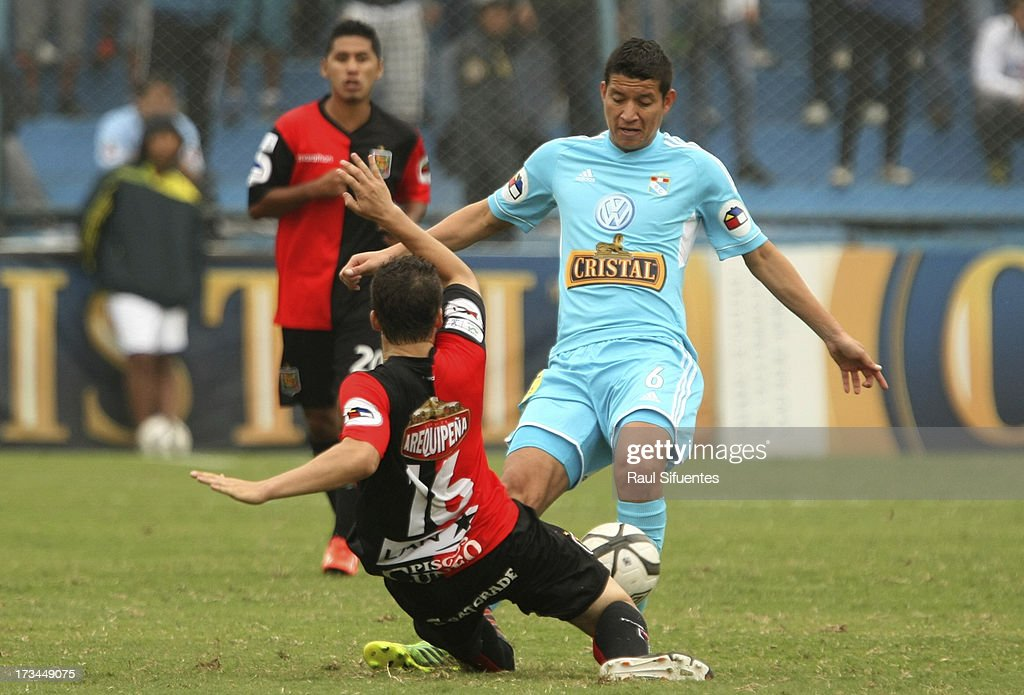 Marcos Delgado (R) of Sporting Cristal fights for the ball with Santiago Bezruk (L) of Melgar FC during a match between Sporting Cristal and Melgar FC as part of the Torneo Descentralizado 2013 at Alberto Gallardo Stadium on July 14, 2013 in Lima, Peru.