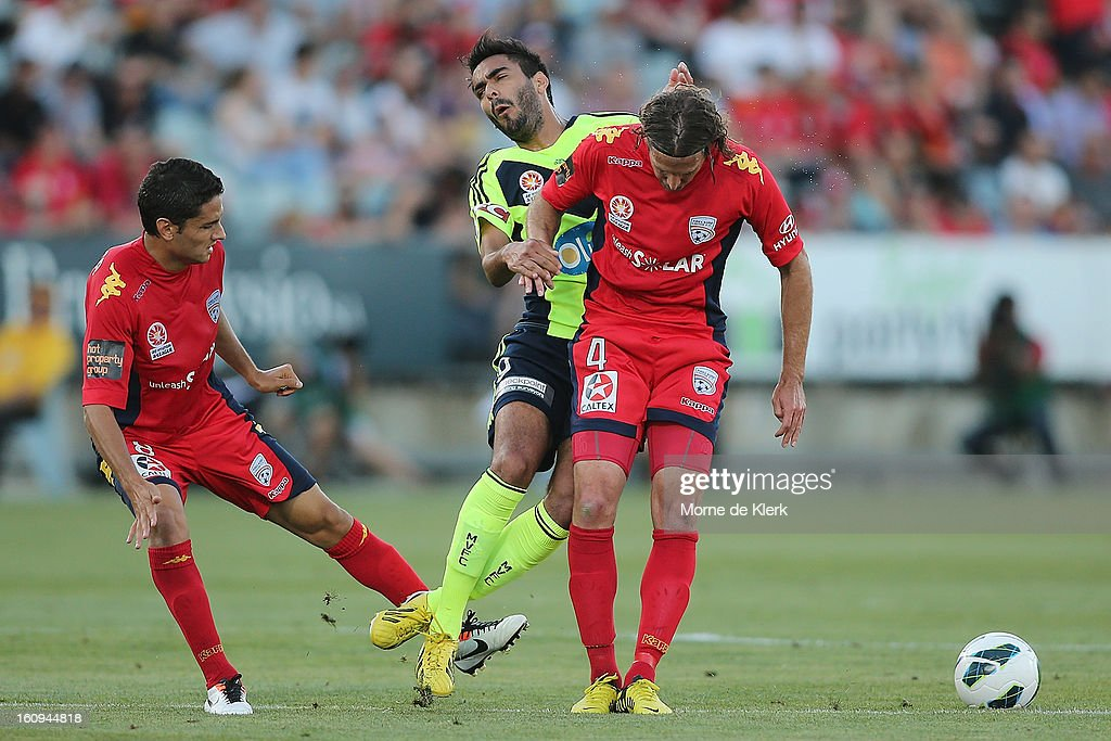 Marcos Flores (C) of Melbourne is tackled by Jonathan McKain (R) of Adelaide during the round 20 A-League match between Adelaide United and the Melbourne Victory at Hindmarsh Stadium on February 8, 2013 in Adelaide, Australia.