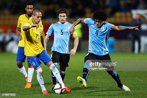 Marcos Guilherme of Brazil evades the challenge of Mauricio Lemos of Uruguay during the FIFA U20 World Cup New Zealand 2015 Round of 16 match between...