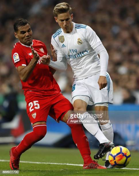 Marcos Llorente of Real Madrid competes for the ball with Gabriel Mercado of Sevilla during the La Liga match between Real Madrid and Sevilla at...