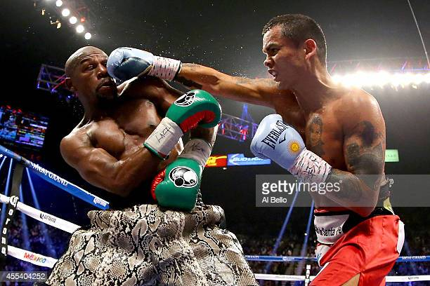 Marcos Maidana throws a right to the face of Floyd Mayweather Jr during their WBC/WBA welterweight title fight at the MGM Grand Garden Arena on...