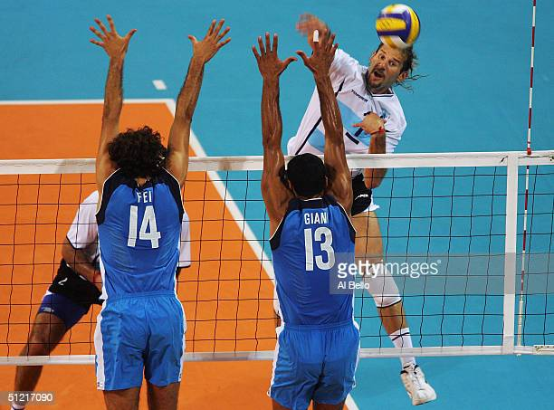 Marcos Milinkovic of Argentina spikes the ball against Alessandro Fei and Andrea Giani in the men's indoor Volleyball quarterfinal match on August 25...