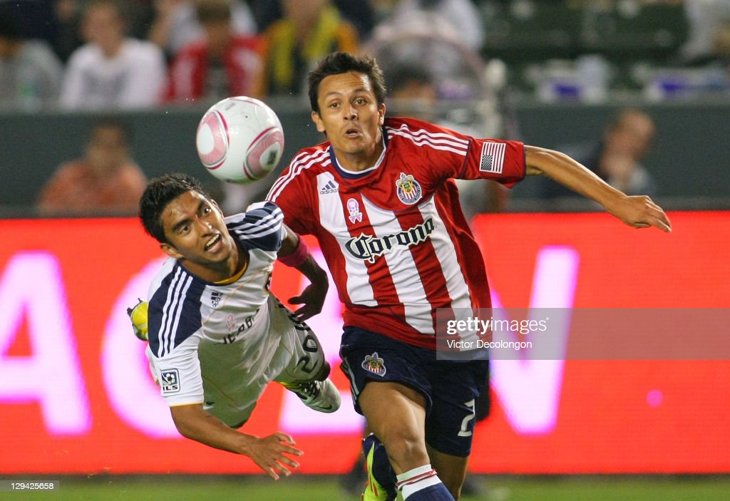Marcos Mondaini of Chivas USA plays the ball past AJ DeLaGarza of the Los Angeles Galaxy in the second half during the MLS match at The Home Depot...
