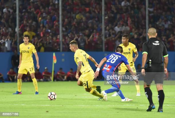 Marcos Riveros of Paraguays Cerro Porteno vies for the ball with Edwin Cardona of Argentina's Boca Juniors during a friendly match at the...