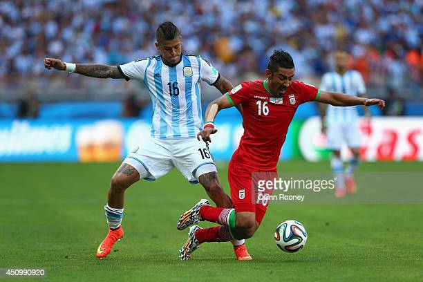 Marcos Rojo of Argentina challenges Reza Ghoochannejhad of Iran during the 2014 FIFA World Cup Brazil Group F match between Argentina and Iran at...