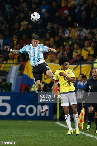 Marcos Rojo of Argentina goes for a header with Juan Guillermo Cuadrado of Colombia during the 2015 Copa America Chile quarter final match between...